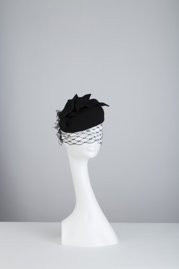 Pillbox headpiece embellished with feather spine, mesh veiling