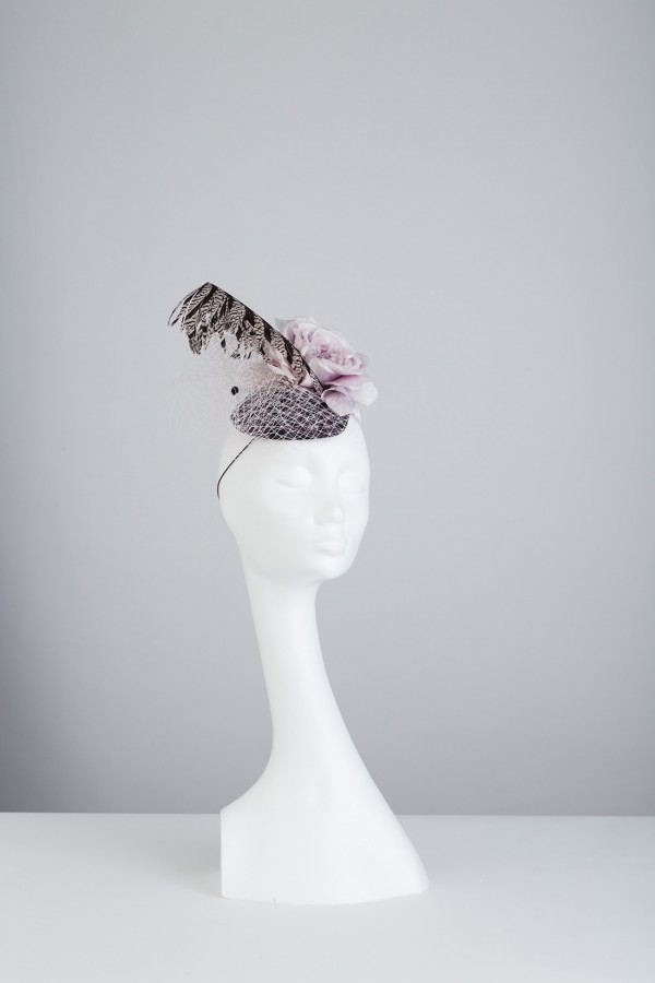 Single navy headpiece embelised with netting, rose and pheaant feather